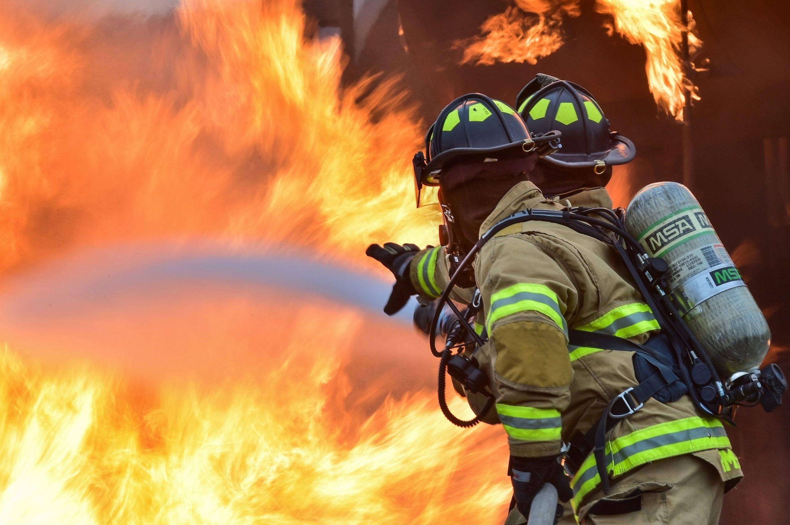 two firefighters hosing a fire